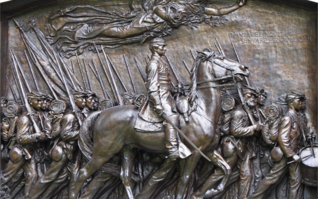 Close up image of a monument with a man on a horse and multiple marking soldiers around him.